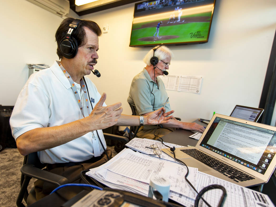 Russ Langer, left, commentates as Jerry Reuss checks some statistics during their radio broadca ...