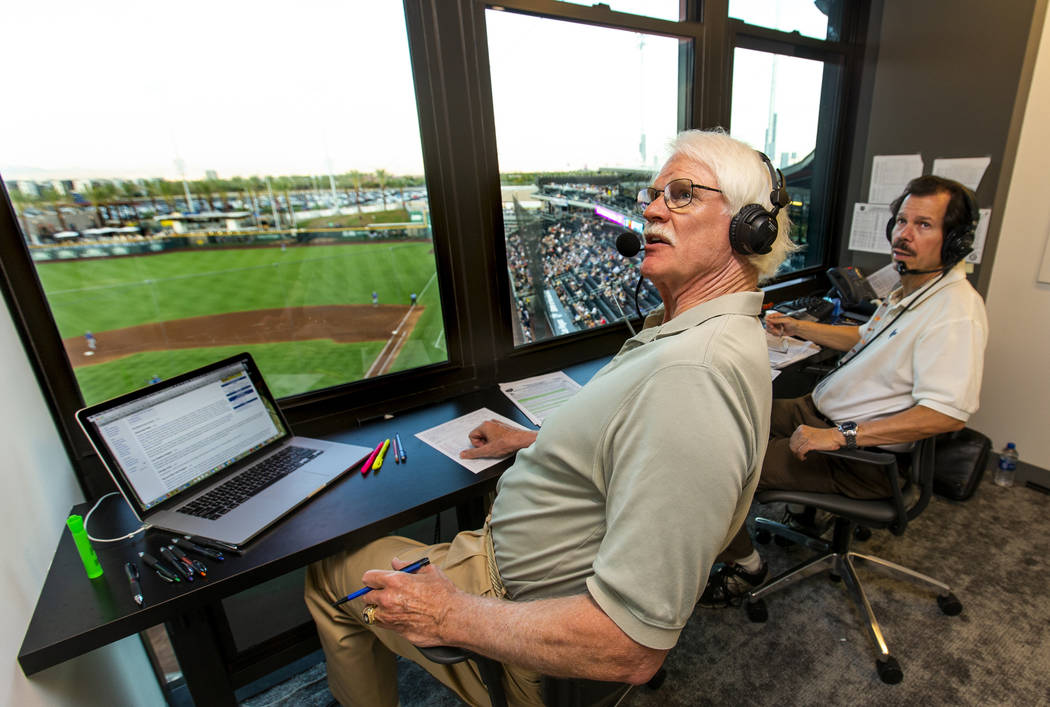Jerry Reuss, left, and Russ Langer look to a video replay for their radio broadcast during the ...