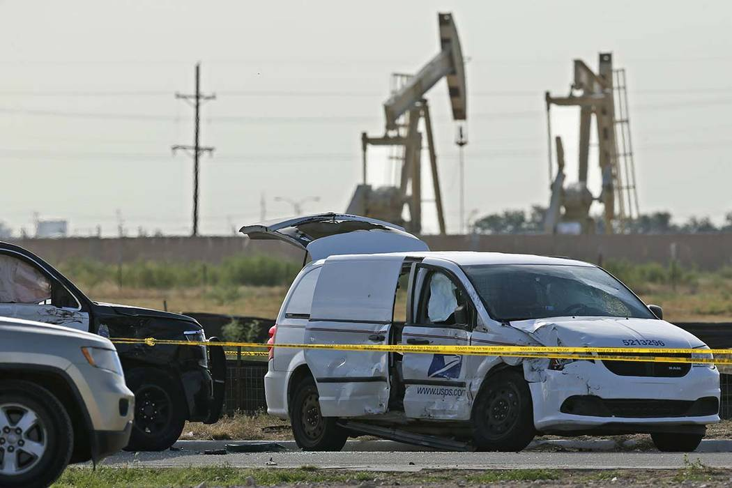 A U.S. Mail vehicle, right, which was involved in Saturday's shooting, is pictured outside the ...