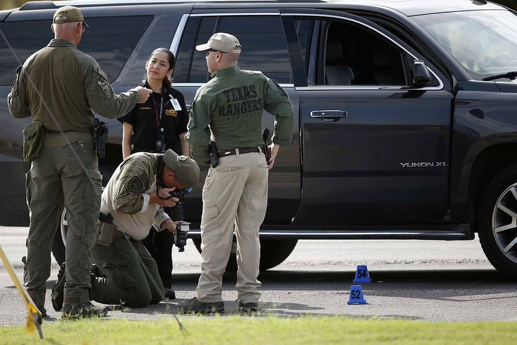Law enforcement officials process a scene involved in Saturday's shooting, Sunday, Sept. 1, 201 ...