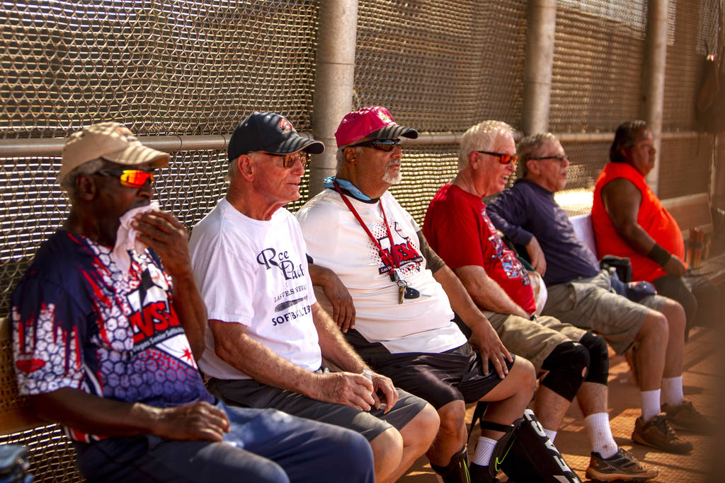 Members of the Las Vegas Senior Softball Association watch the inning of a play during a baseba ...