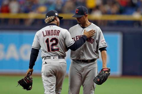 Cleveland Indians shortstop Francisco Lindor (12) pats Indians pitcher Carlos Carrasco on the c ...