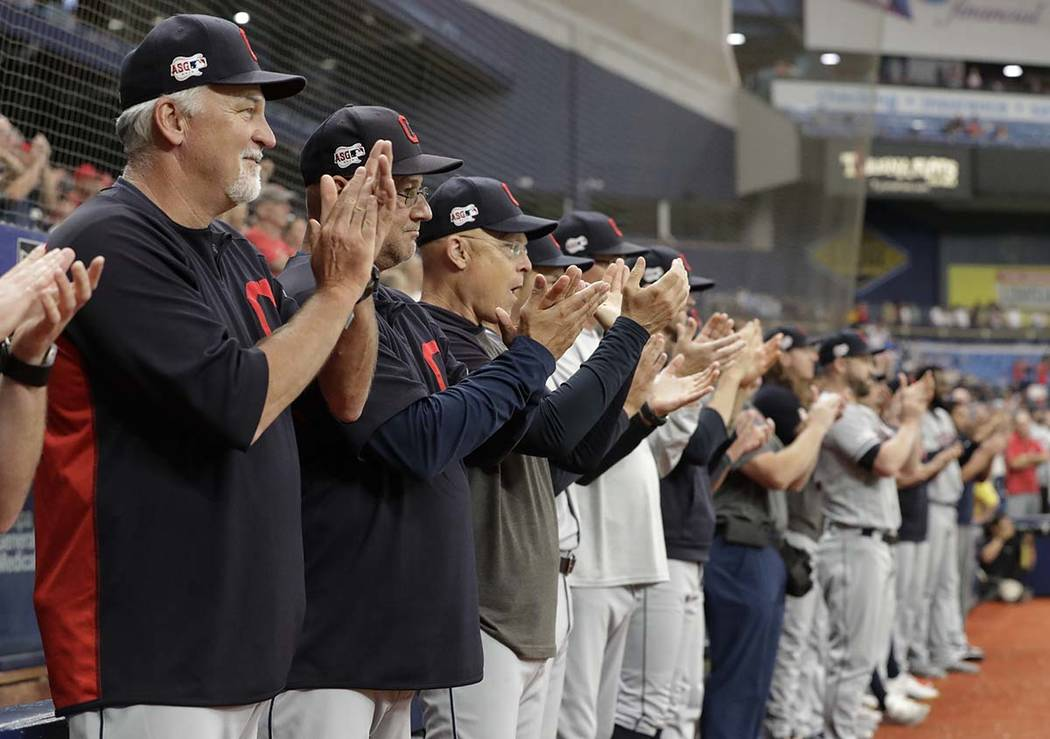 Cleveland Indians players and coaches applaud as pitcher Carlos Carrasco warms up during the se ...
