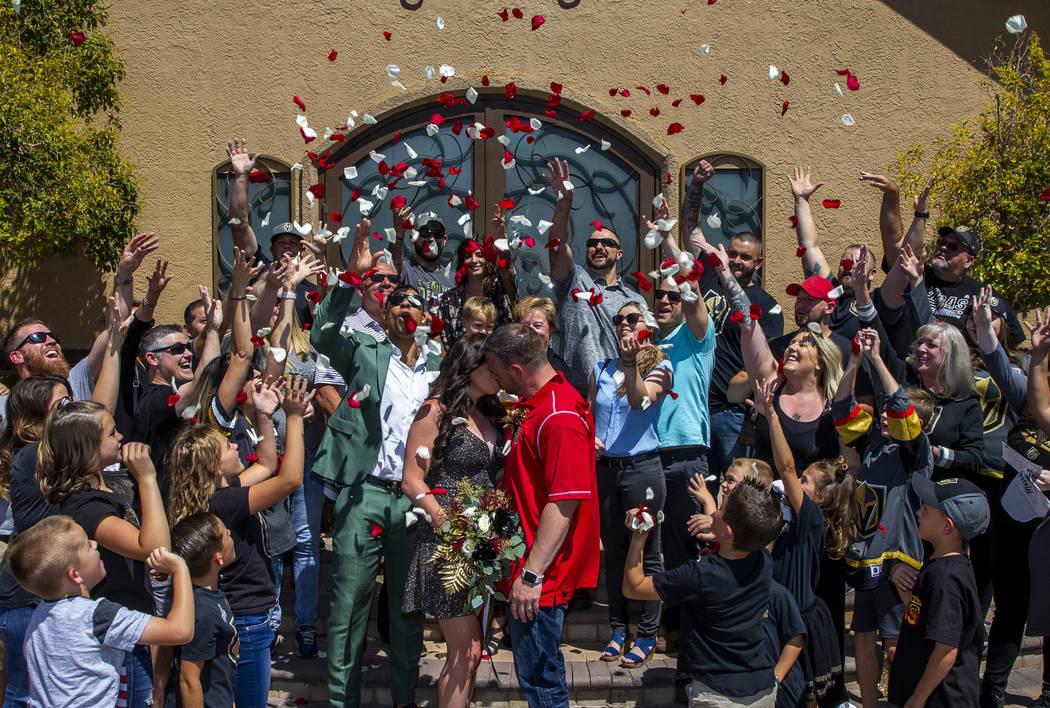 Guests toss flower petals as Laura and Justin Long kiss beside Vegas Golden Knights player Ryan ...