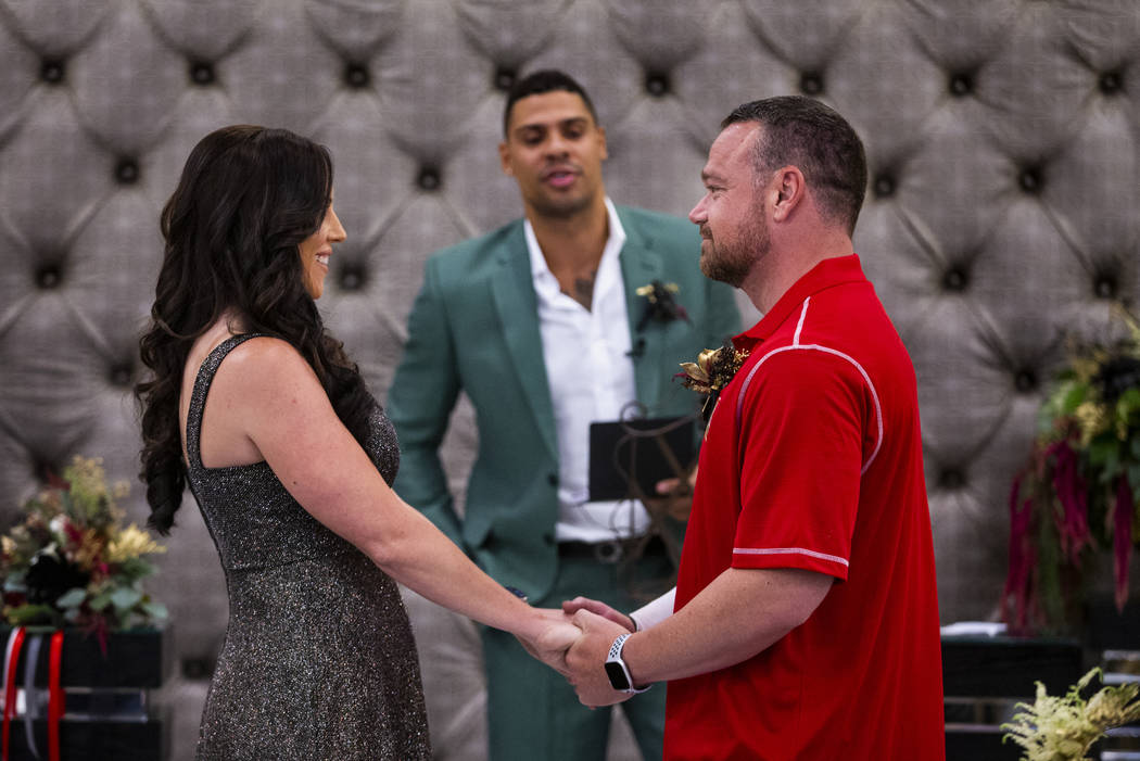 Laura and Justin Long hold hands as Vegas Golden Knights player Ryan Reaves, center, conducts a ...