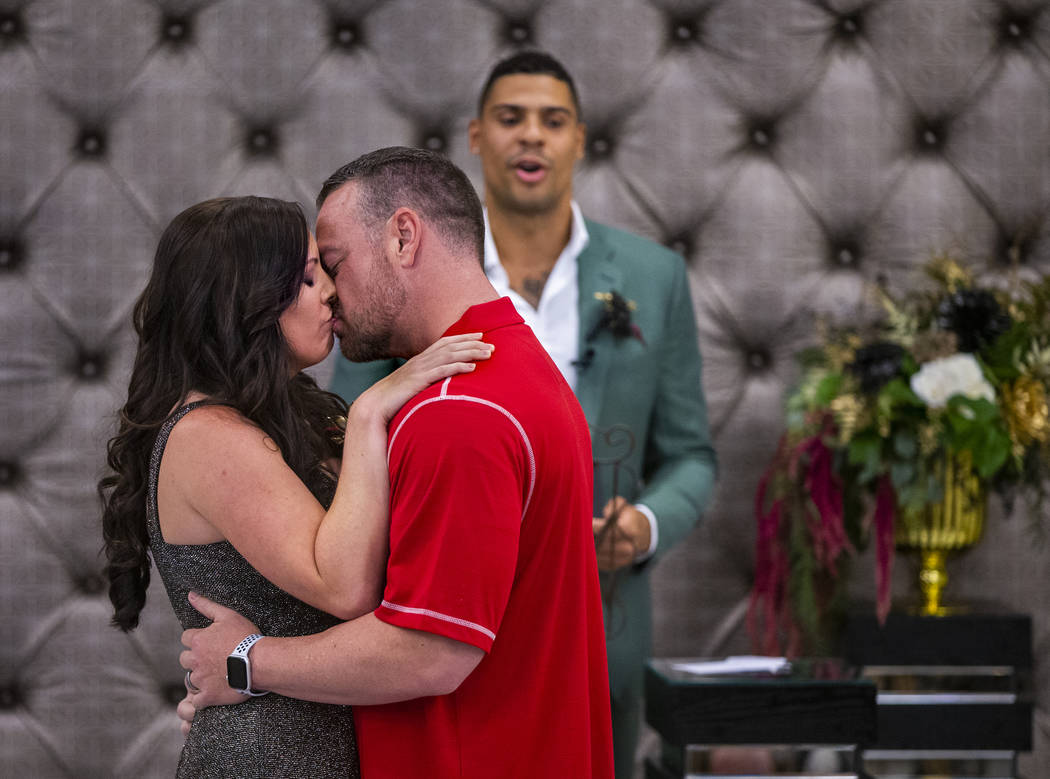 (From left) Laura and Justin Long kiss as Vegas Golden Knights player Ryan Reaves finishes cond ...