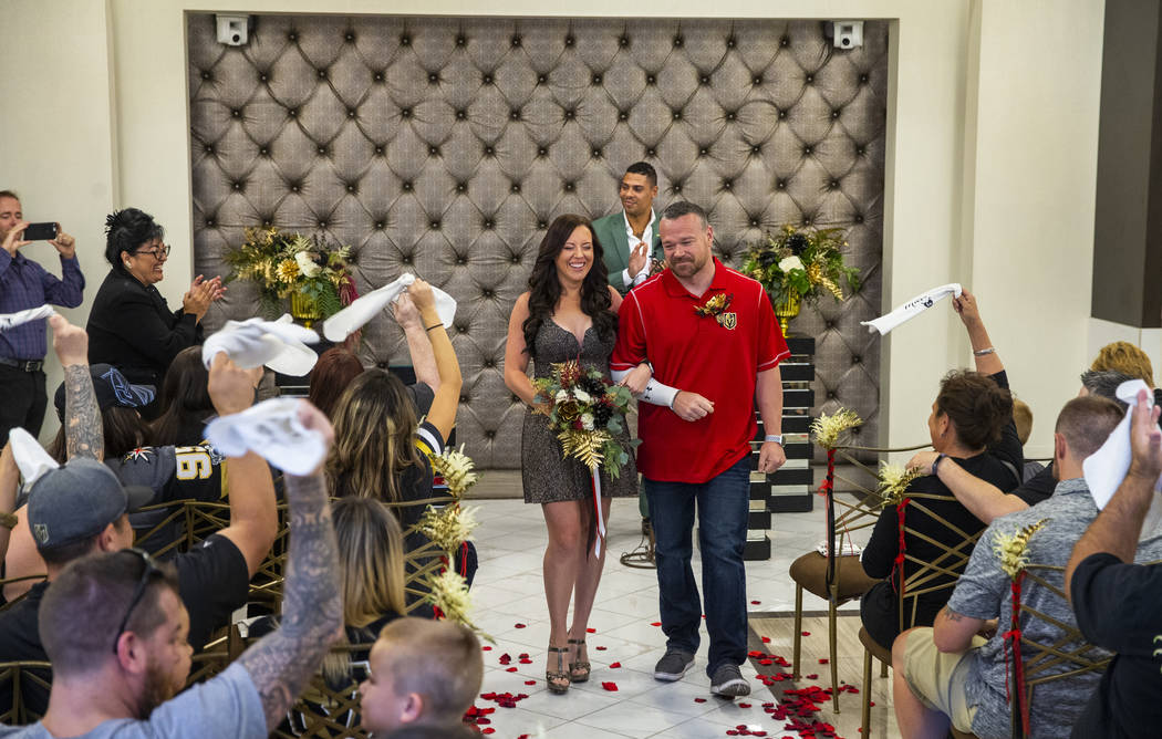 Laura and Justin Long walk back down the aisle after Vegas Golden Knights player Ryan Reaves, c ...