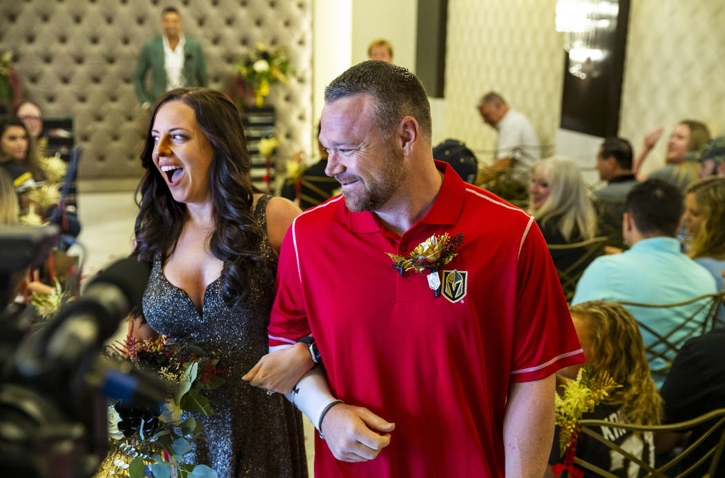 Laura and Justin Long walk back down the aisle after Vegas Golden Knights player Ryan Reaves, r ...