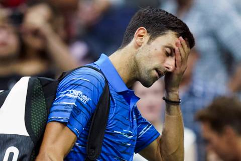 Novak Djokovic, of Serbia, walks off the court as he retires during his match against Stan Wawr ...