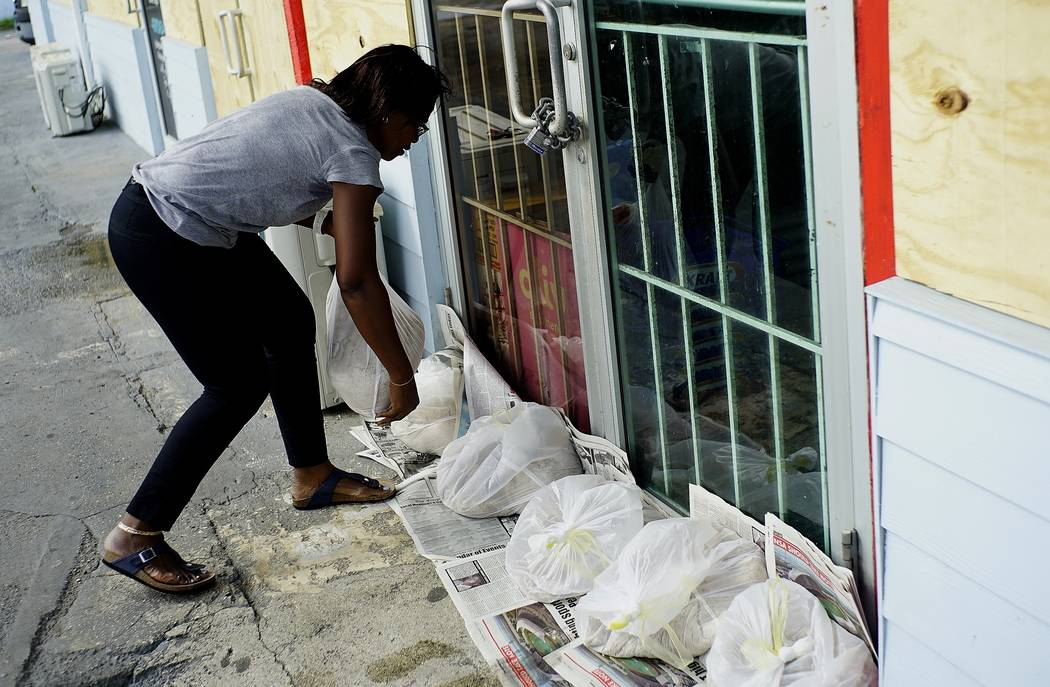 Yolande Rolle puts sandbags at her shop's doorstep as she prepares for the arrival of Hurricane ...
