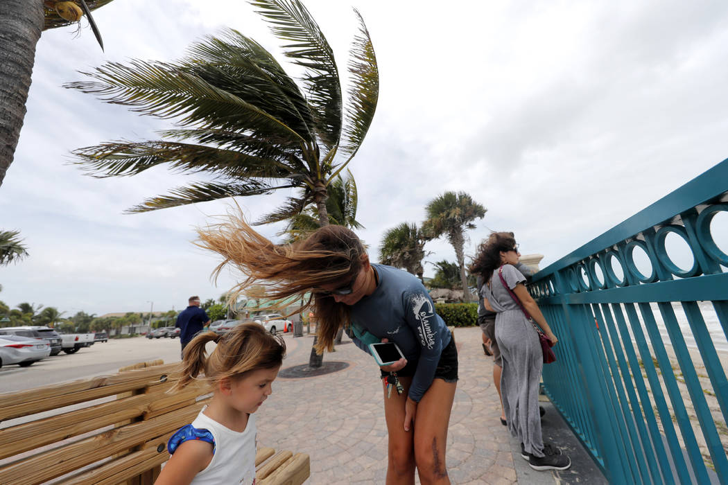 Kristen Davis watches the high surf from a boardwalk overlooking the Atlantic Ocean with her da ...