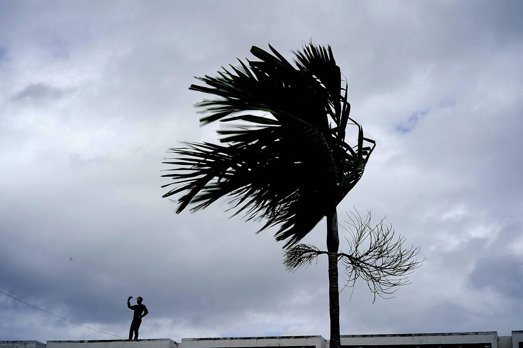 A man stands on a store's roof as he works to prepare it for the arrival of Hurricane Dorian in ...