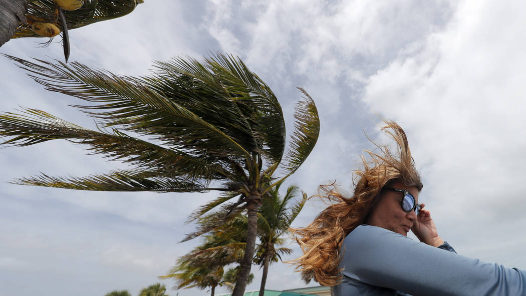 Kristen Davis watches the high surf from a boardwalk overlooking the Atlantic Ocean, as winds f ...