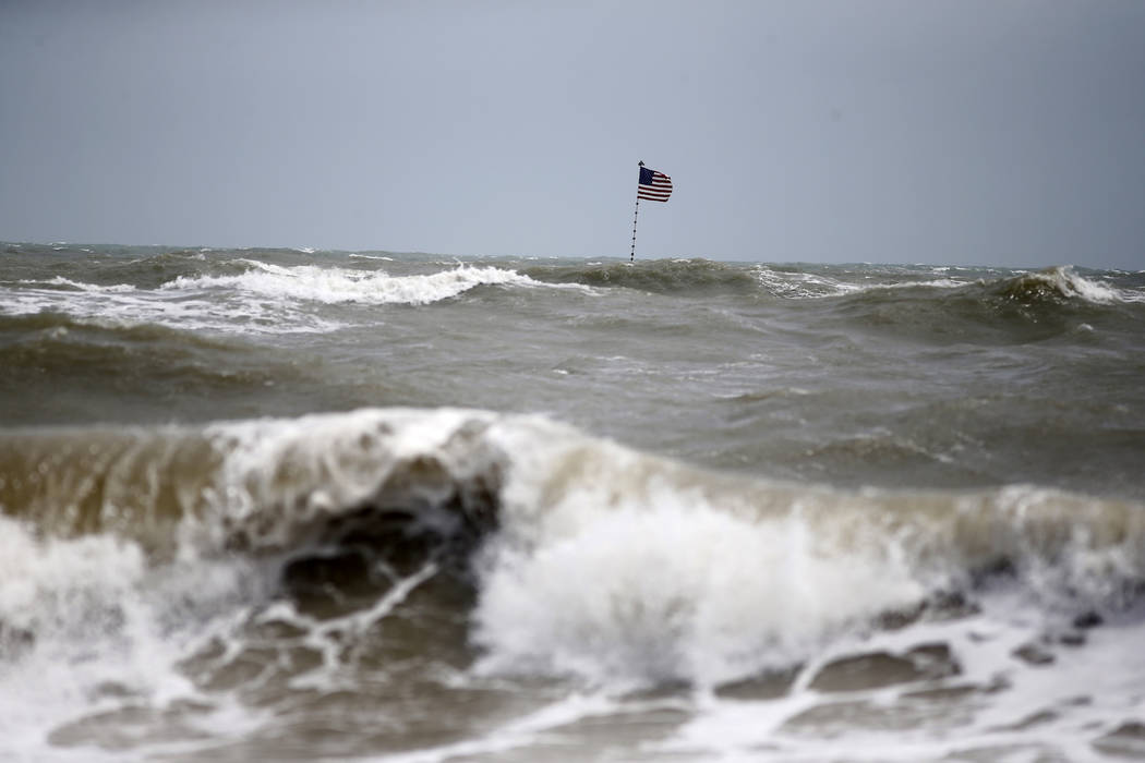 Waves crash in front of an American flag that is planted on a jetty during a high surf from the ...
