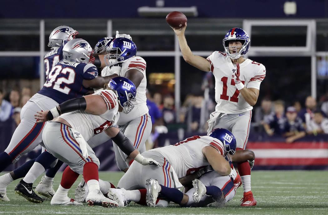 New York Giants quarterback Kyle Lauletta (17) passes under pressure from New England Patriots ...