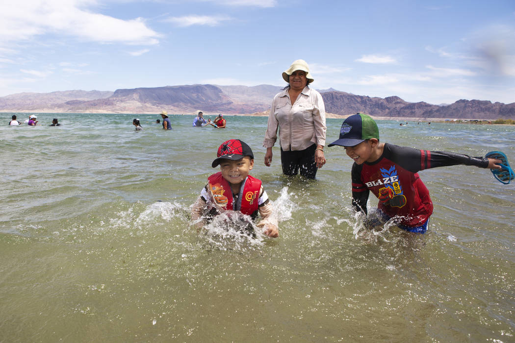 Jaiden Sanchez, 4, left, and his brother Jason, 7, right, splash in the water as their aunt Noe ...