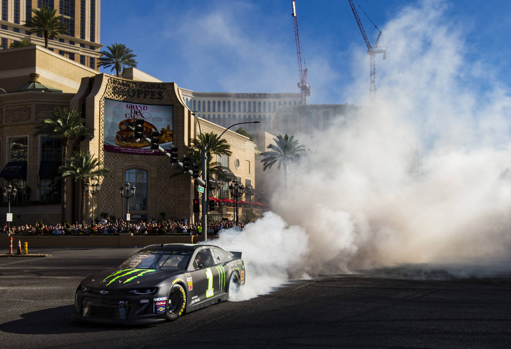 Kurt Busch performs a burnout during the NASCAR America Burnout Boulevard event on the Las Vega ...
