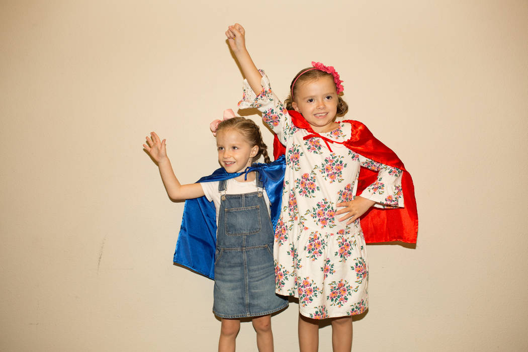 At right, Superhero Ambassador Navy Bishop, 6, and her younger sister Riley wear their superher ...