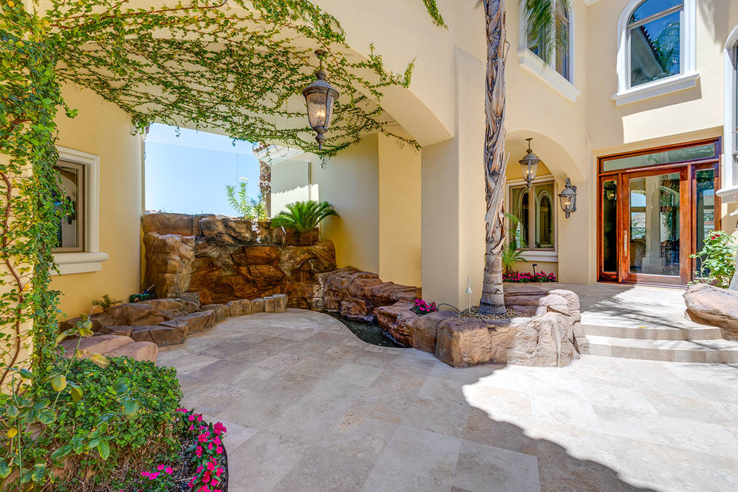 The entrance to the home features a courtyard with a waterfall. (Ivan Sher Group)
