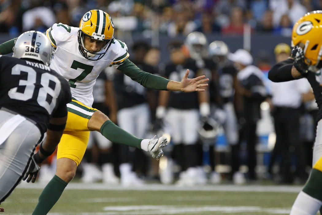Green Bay Packers' Sam Ficken (7) kicks a field goal under pressure from Oakland Raiders' Keise ...