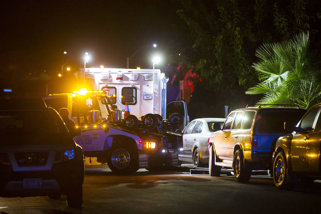 A tow truck prepares to move a vehicle blocking a driveway as Las Vegas police search a Spring ...