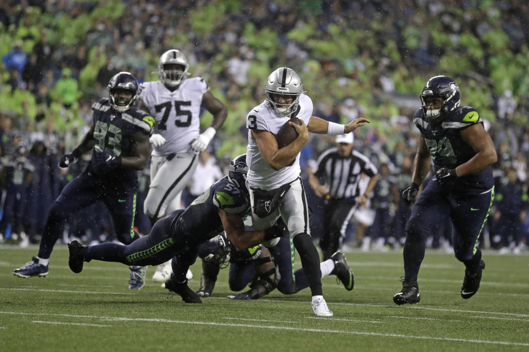 Oakland Raiders quarterback Nathan Peterman (3) scrambles, but Seattle Seahawks linebacker Cody ...
