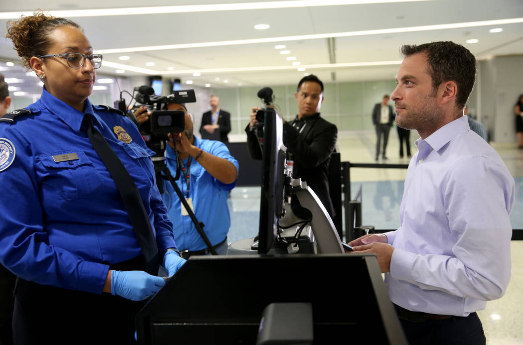 Transportation Security Officer Terry demonstrates Credential Authentication Technology with To ...
