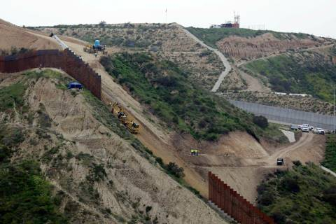 FILE - In this March 11, 2019 photo, construction crews replace a section of the primary wall s ...