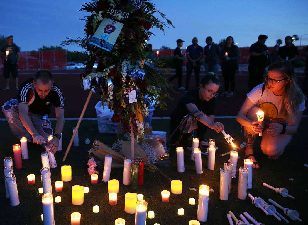Brian Roberts, left, Carly Blemishes and Deidre Evans light candles during a vigil for Malik No ...