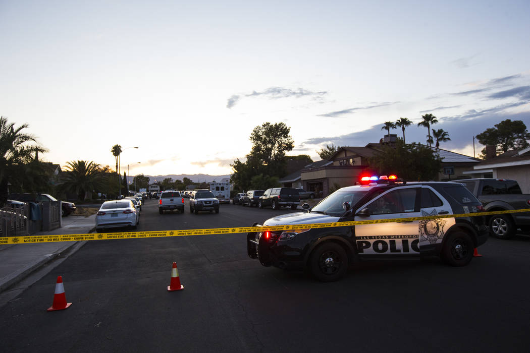 Las Vegas police secure the area around a residential street as they wait for a search warrant ...