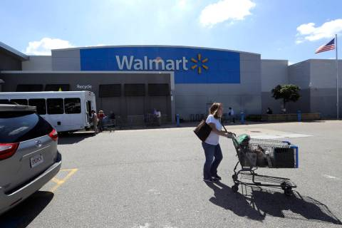 A customer pushes a shopping cart Tuesday, Sept. 3, 2019, outside a Walmart store, in Walpole, ...