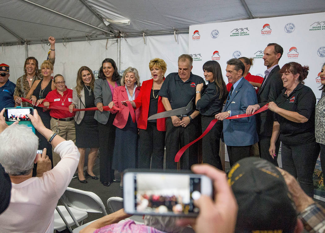 Dr. Arnold Stalk, center, president of Veterans Village, cuts a ribbon during the grand opening ...