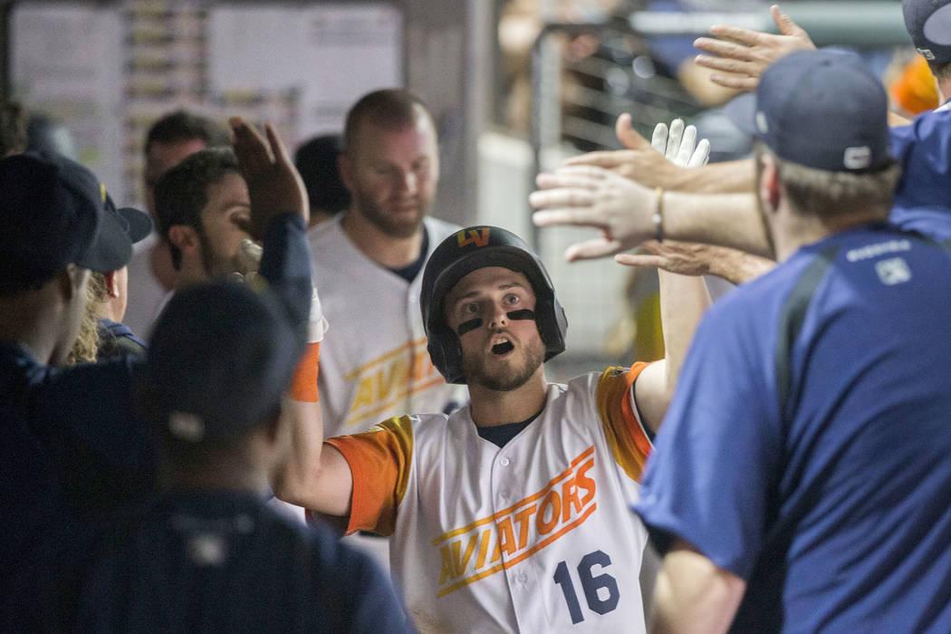 Las Vegas Aviators left fielder Mark Payton (16) celebrates with teammates after Payton hit a h ...