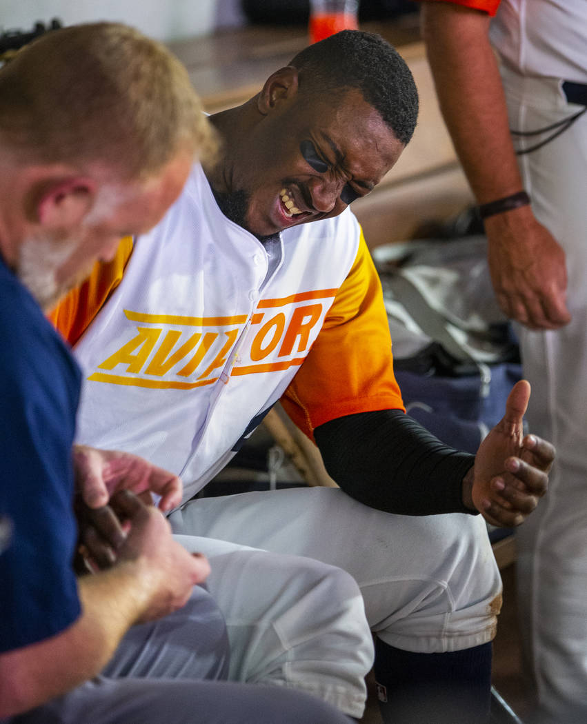 Las Vegas Aviators shortstop Jorge Mateo (14) winces in pain while being checked out by the tra ...