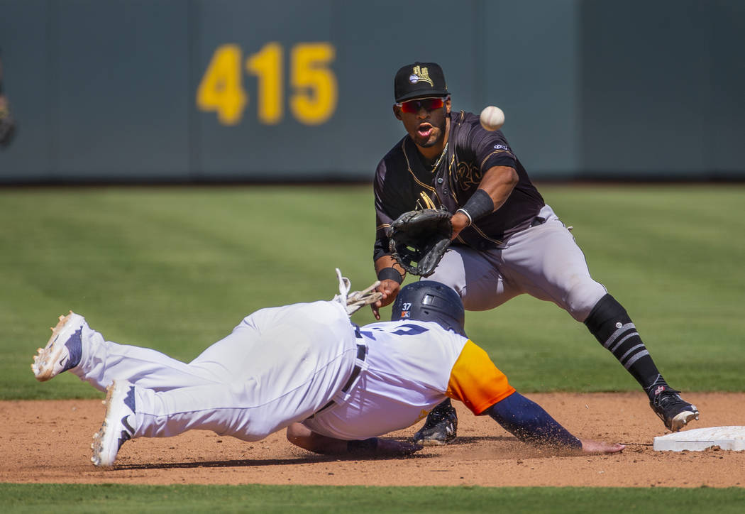 Las Vegas Aviators catcher Cameron Rupp (37, left) dives safely back to second just under a thr ...