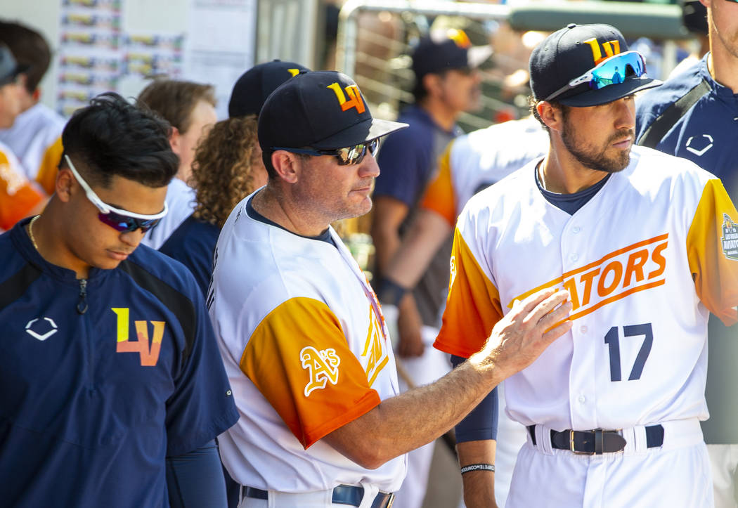 Las Vegas Aviators manager Fran Riordan (39, center) confers with first baseman Alfonso Rivas ( ...