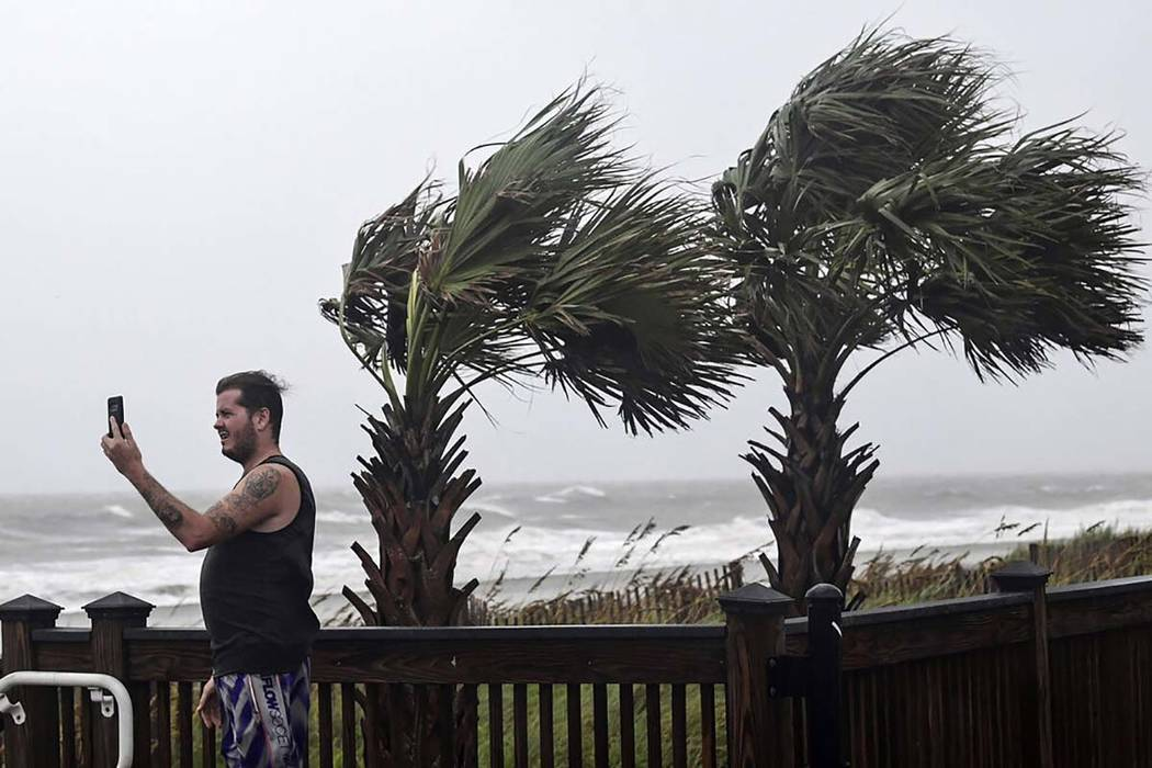 William Ellinge, of Murrells Inlet, S.C., takes photos of waves crashing on the shore in Myrtle ...