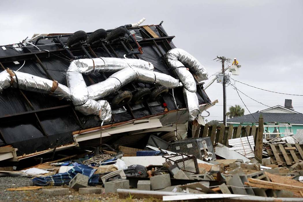 Power company lineman work to restore power after a tornado hit Emerald Isle, N.C. as Hurricane ...