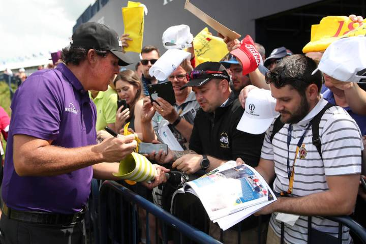 Phil Mickelson of the United States signs autographs on the 18th fairway during a practice roun ...