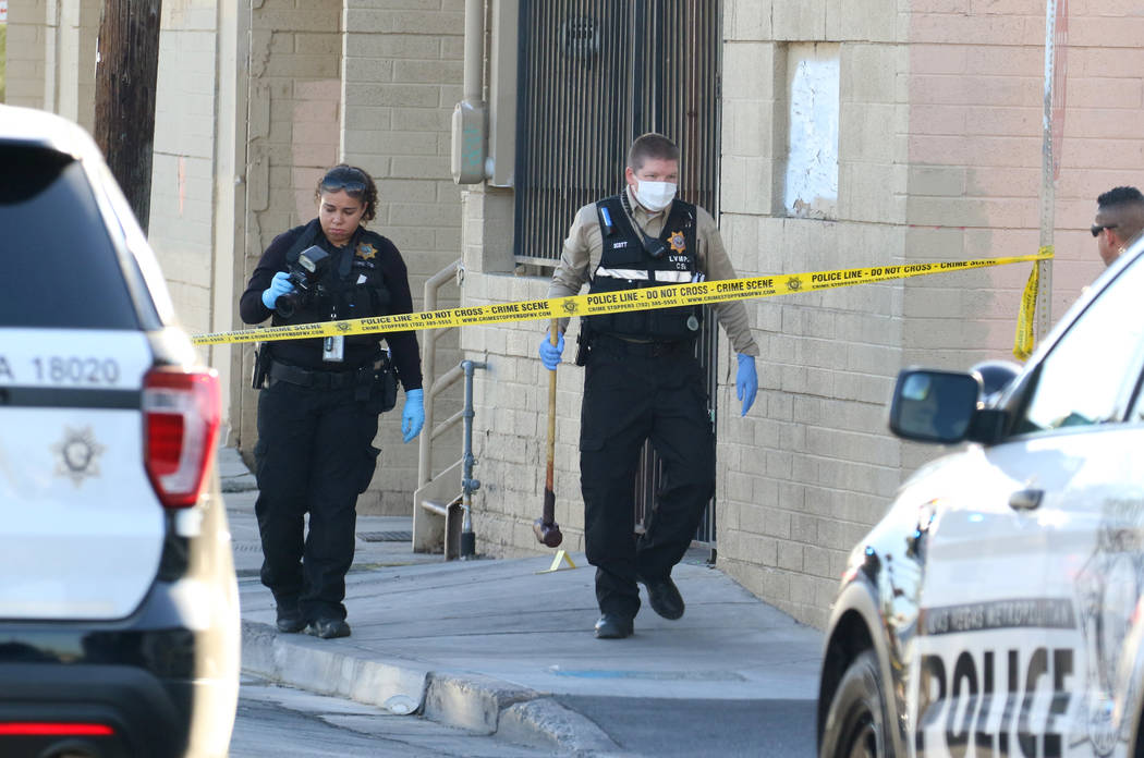Las Vegas police collect evidence after a woman was killed with a sledgehammer on the 1000 bloc ...