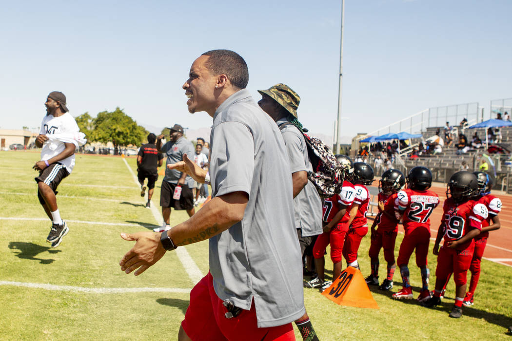Devin Conway celebrates with coaches during a play made by TMT Red Lions players at Bonanza Hig ...