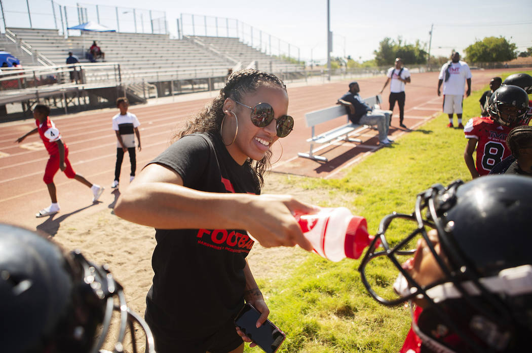 Alvina Conway, left, supplies water for TMT Red Lions player Anthony Rebel, right, and other p ...