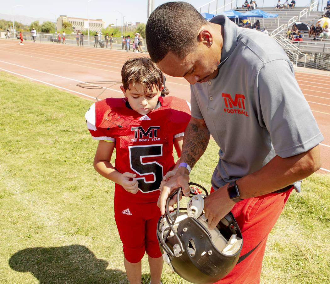Devin Conway, right, fixes the helmet of TMT Red Lions player Noah Hamly, 8, during a youth foo ...
