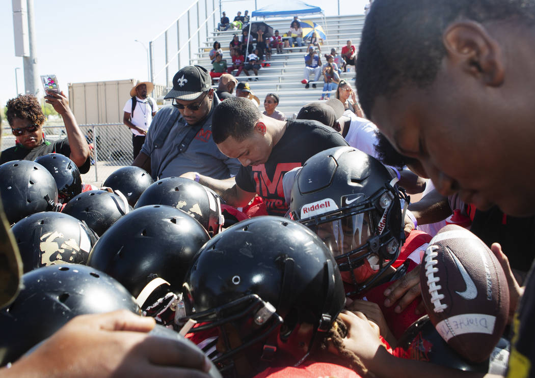 Devin Conway, center, prays with TMT Red Lions players and coaches at Bonanza High School on Sa ...