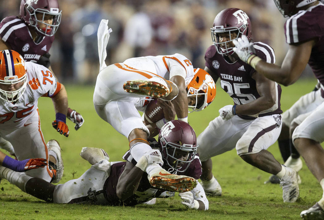 Texas A&M linebacker Otaro Alaka (42) upends Clemson quarterback Kelly Bryant (2) after a s ...