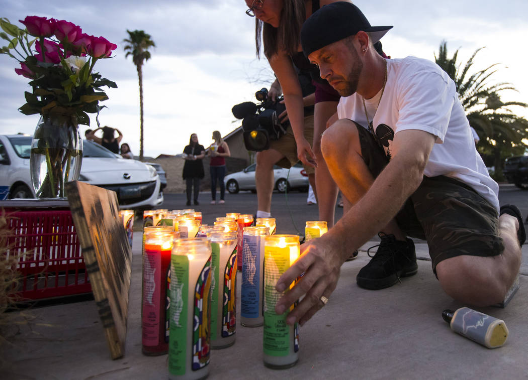 Ted Hamilton lights candles before the start of a vigil in memory of Jennifer Ratay outside of ...
