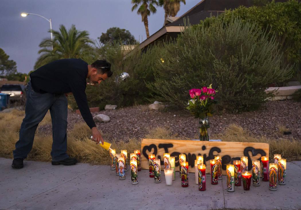 Carlos Gonzalez, a longtime family friend of Jennifer Ratay, lights a candle before the start o ...