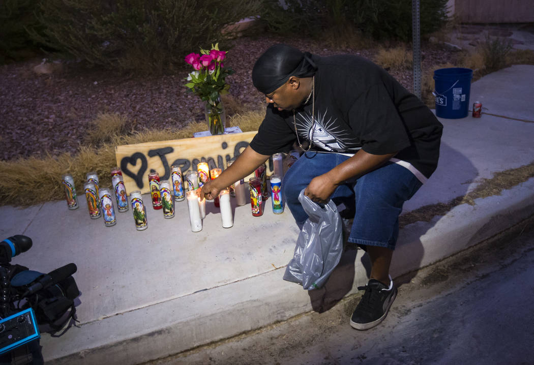 Mario Smith lights candles in memory of Jennifer Ratay during a vigil outside of the home where ...