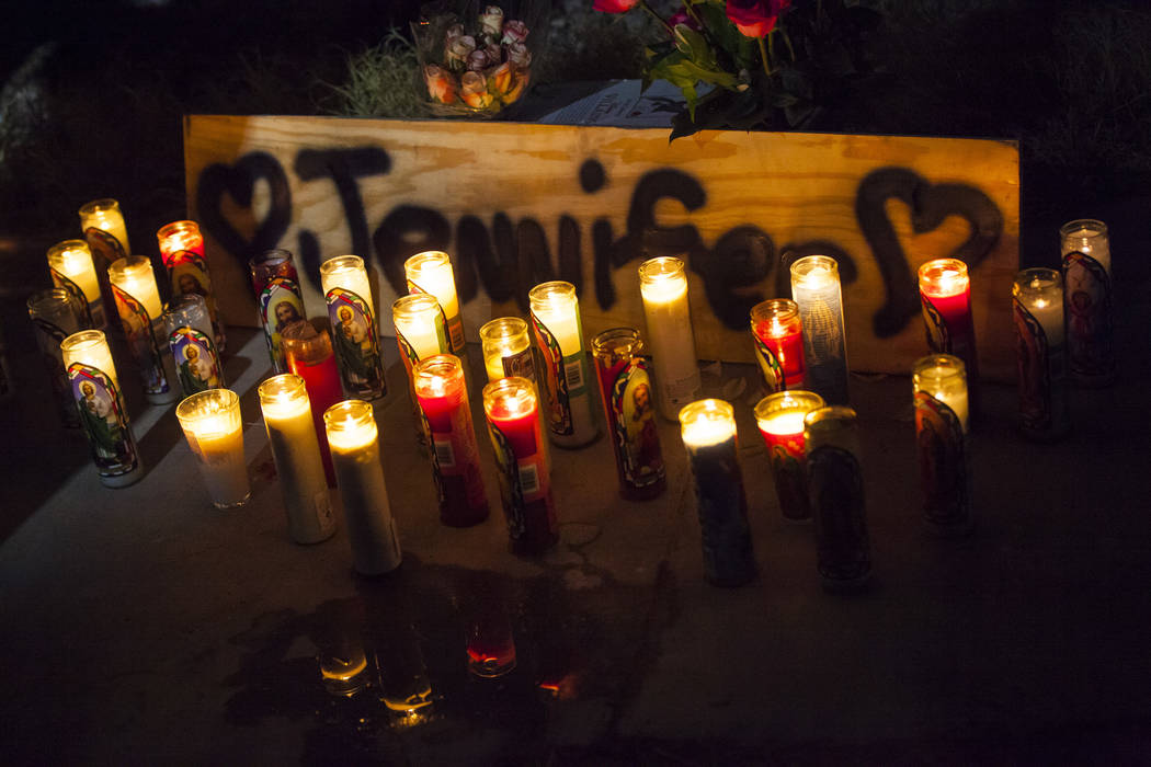 Candles light a sign during a vigil in memory of Jennifer Ratay outside of the home where she w ...