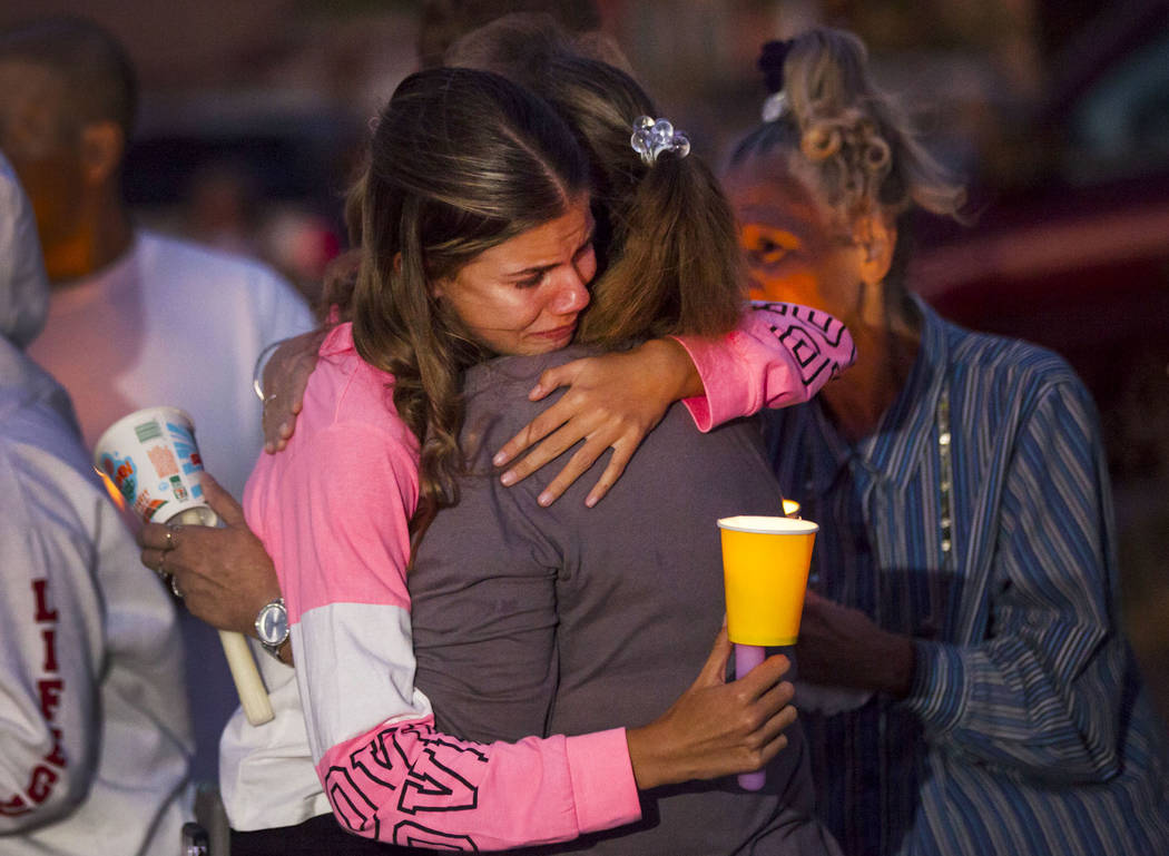 Kelsi Jackson, 15, center left, is comforted during a vigil in memory of her mother, Jennifer R ...